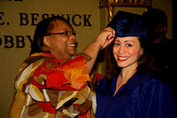 Michelle Stewart, Manager of Professional Services, helps graduates don their caps