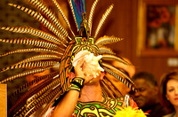 A performer with Eztli Chicahua, a traditional Aztec Dance Group, blows on a shell as he displays his very colorful headdress.